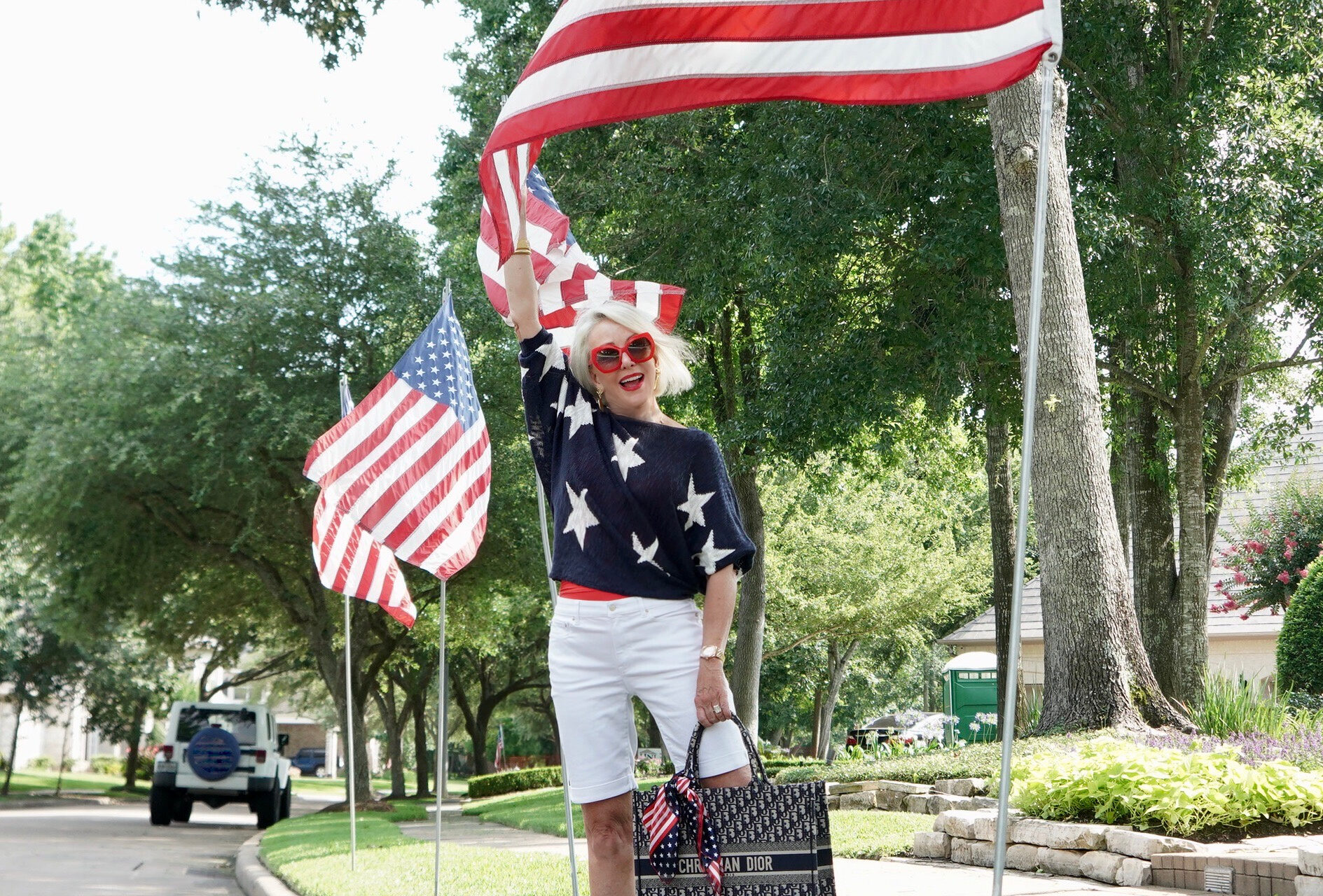 Sheree Frede of the SheShe Show standing by American Flags wearing white shorts and navy sweater with white stars