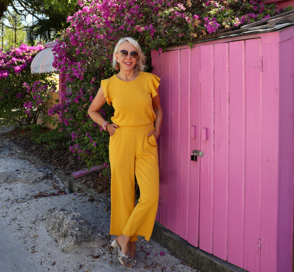Sheree Frede of the SheShe Show standing in front of pink wall wearing a yellow pants outfit