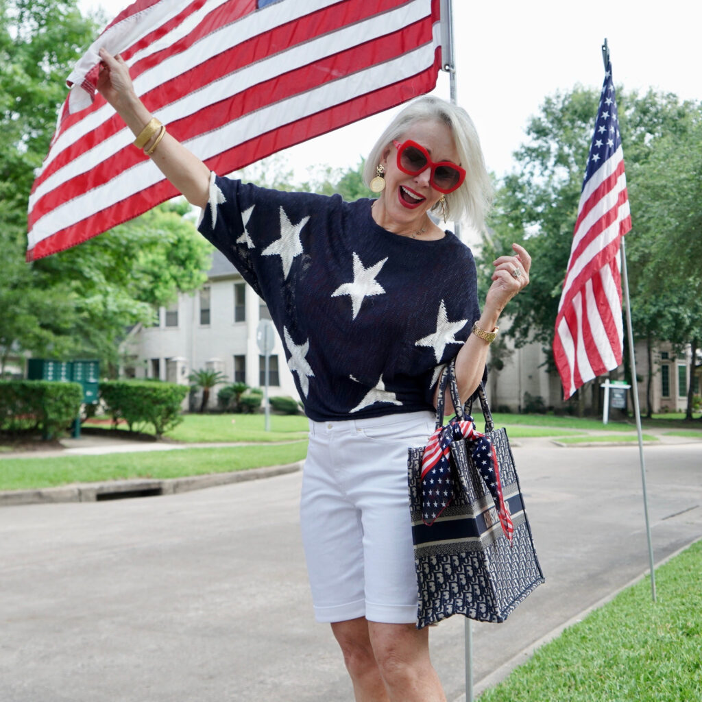 Sheree Frede of the SheShe Show standing by American flags  wearing a navy and white star sweater