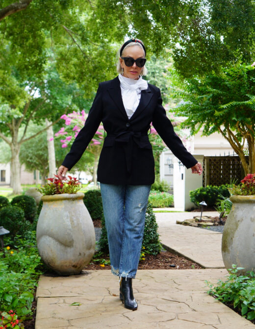 Sheree Frede of the SheShe Show standing on sidewalk wearing bule jeans, black blazer, and white bow blouse
