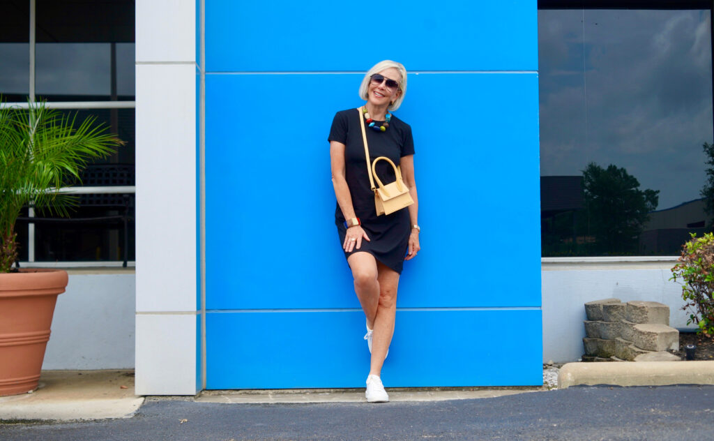 Sheree Frede of the SheSheShow standing in front of blue wall wearing a black short sleeve t-shirt dress