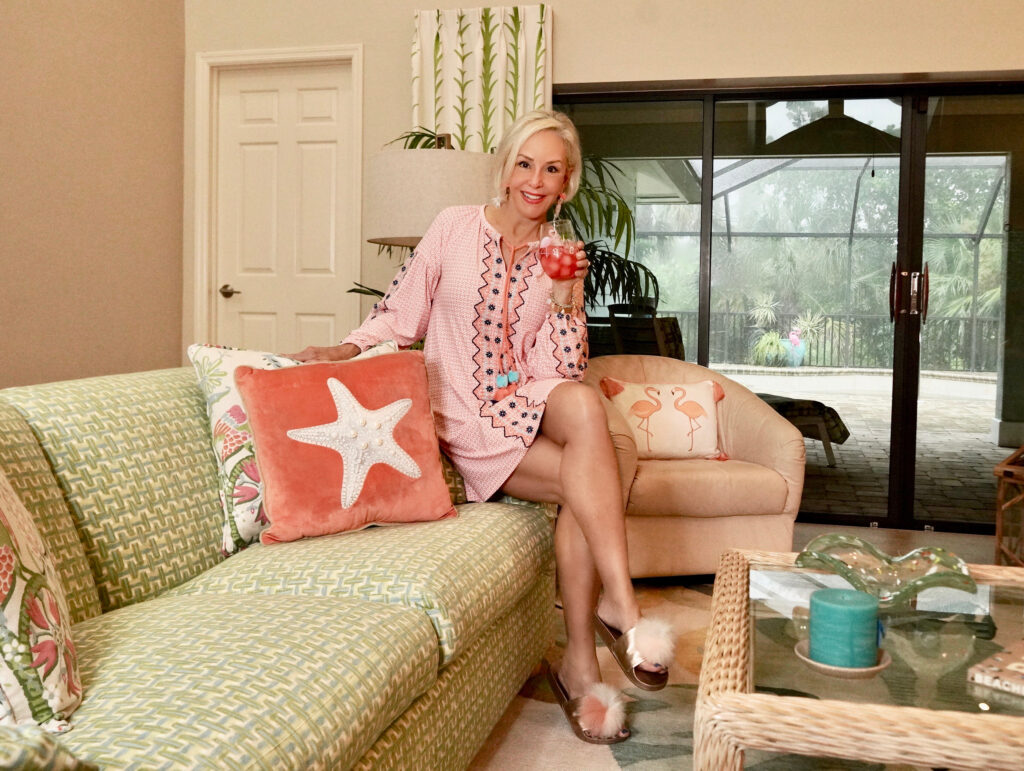 Sheree Frede with the SheShe Show sitting in living room wearing a coral and white print dress with tassel tie