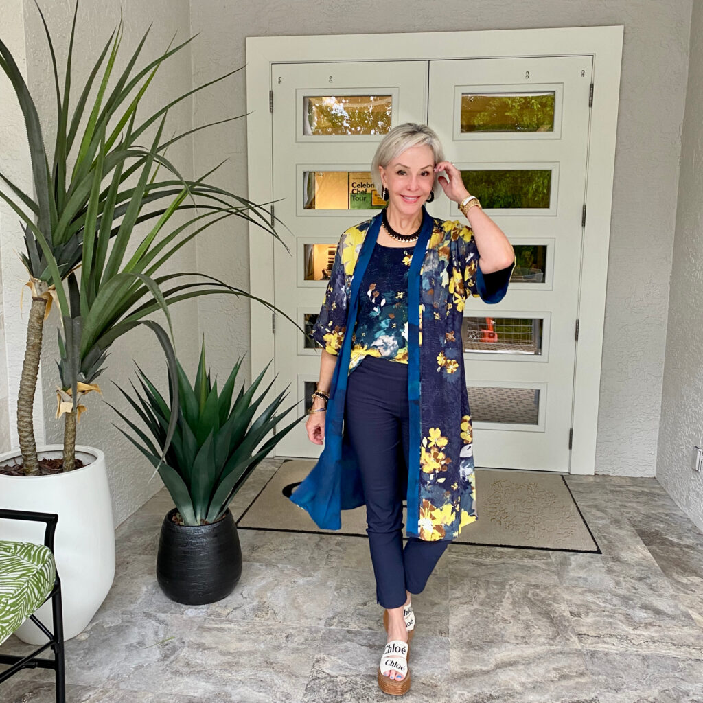 Sheree Frede of the SheShe Show standing in front of double doors wearing a navy kimono and navy pants