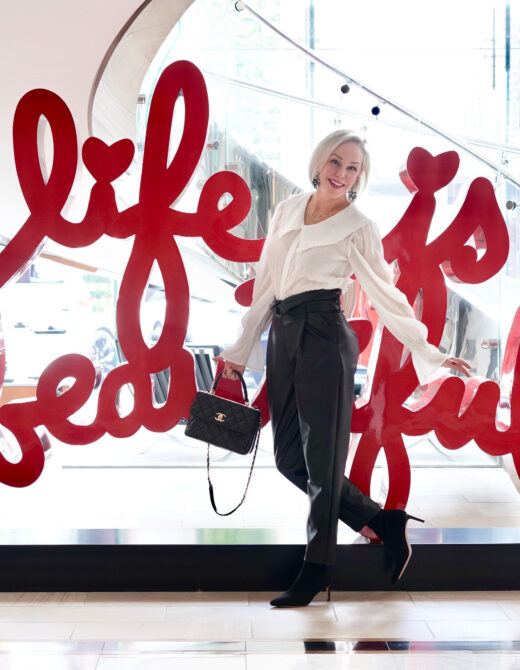 Sheree Frede of the SheShe Show standing in front of Life is Beautiful Sign wearing black faux leather joggers and feminine white top