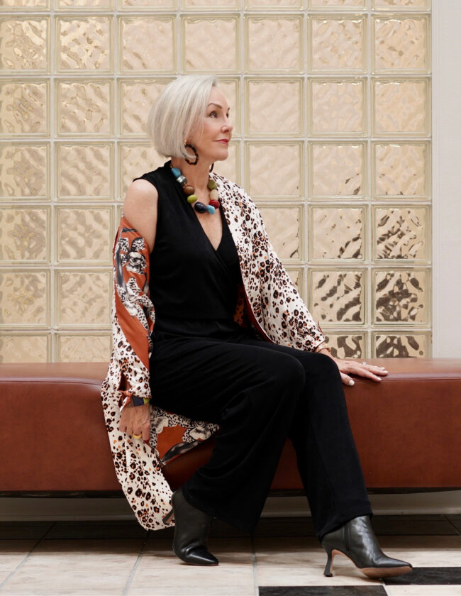 Sheree Frede of the SheShe Show wearing a black jumpsuit and burnt orange print kimono