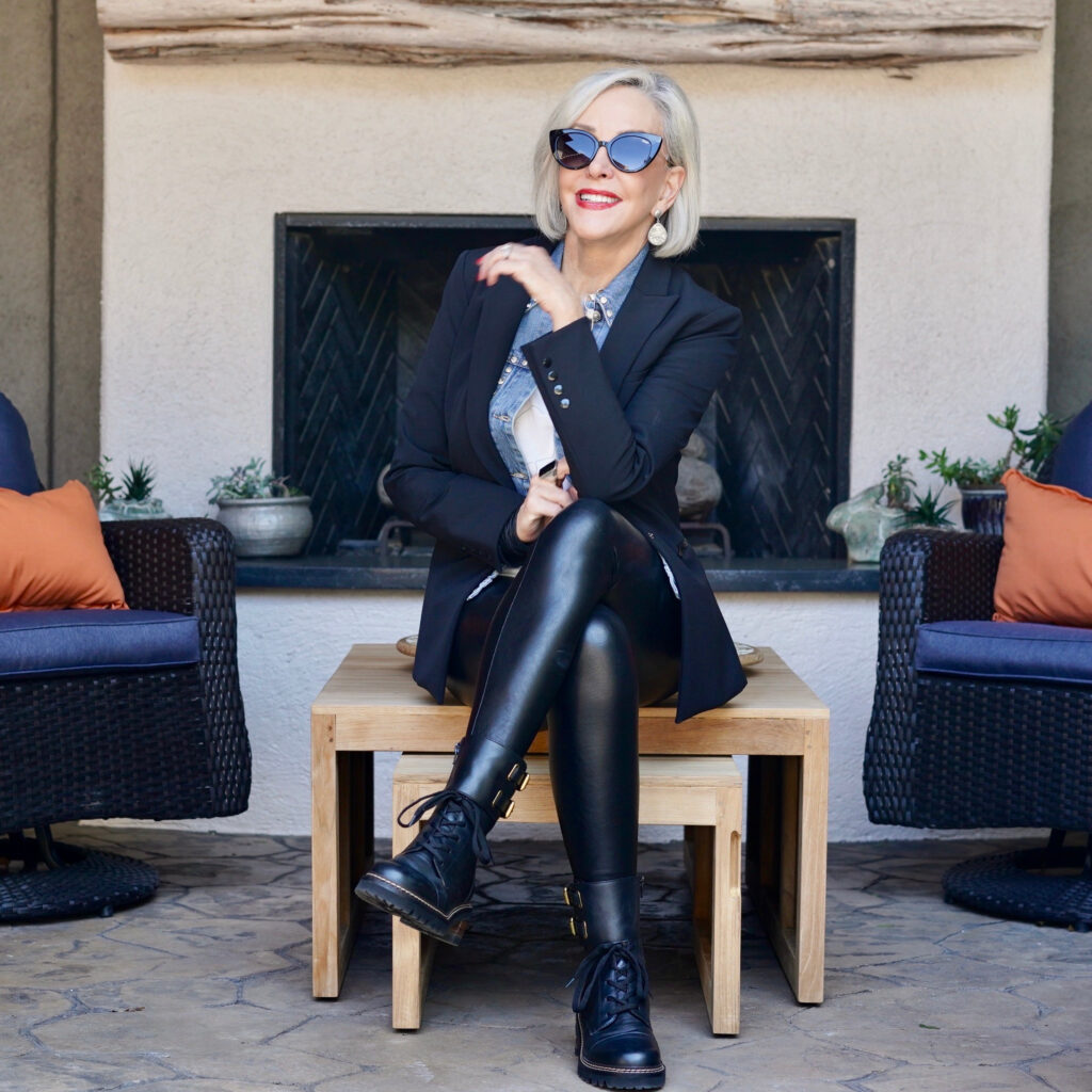 Sheree Frede of the SheShe Show standing in front of outdoor fireplace wearing black blazer and, faux leather jeggings and combat boots.